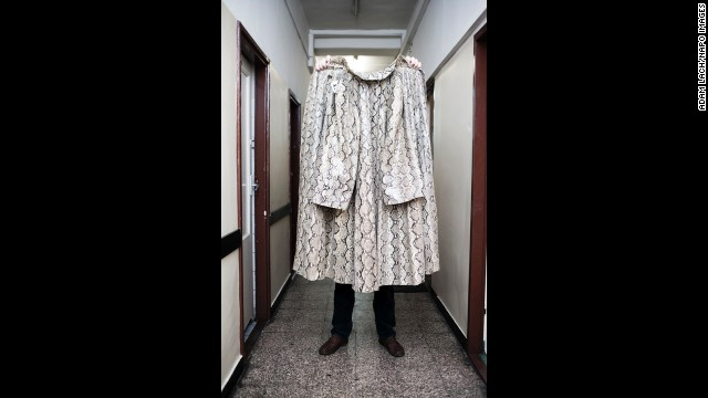 """A snake skin coat is held up in Warsaw. """"This project aims to show human arrogance and folly and to build in us humility,"""" Lach said."""