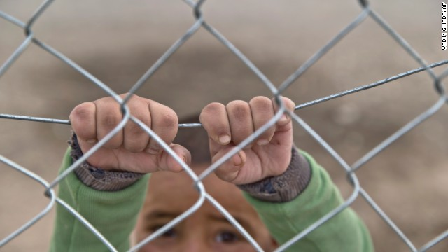 A Kurdish child from the Kobani area holds on to a fence at a refugee camp in Suruc on Sunday, November 16.