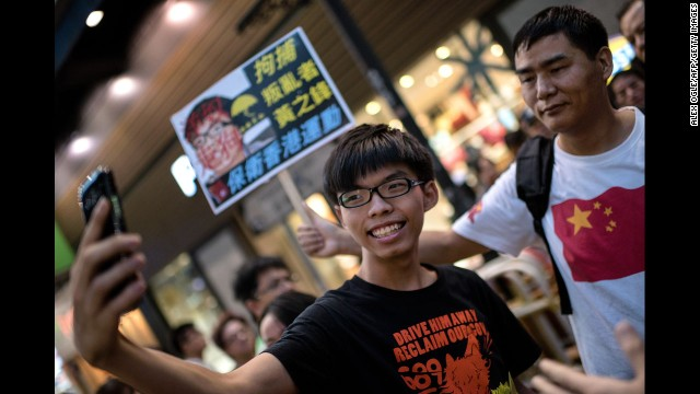 Student activist Joshua Wong snaps a photo next to a pro-Beijing activist who had been shouting slogans at him while he handed out flyers in Hong Kong on Sunday, November 16. Wong founded the pro-democracy student group Scholarism. <a href='http://www.cnn.com/2014/09/21/world/asia/hong-kong-joshua-wong-democracy-protest/'>His goal </a>is to pressure China into giving Hong Kong full universal suffrage.