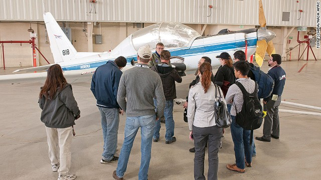 Grindle shows off a YO-3 support research aircraft. The plane is recognizable due to its slow-speed wooden propeller and long wings.