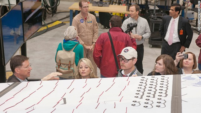 NASA's ongoing project -- the Adaptive Compliant Trailing Edge project, or ACTE -- could save hundreds of millions of dollars a year in fuel costs. NASA test pilot Tim Williams (rear left) discusses an adaptive wing flap on a Gulfstream III.
