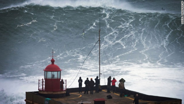 People watch a surfer ride a wave off the coast of Praia do Norte near Nazare, Portugal. The fishing village features a 16,000-foot-deep underwater canyon, churning up some of the largest and most dangerous waves on the planet. Today's big-wave surfers are often towed onto massive waves by jet skis or helicopters.