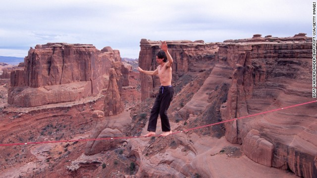 Dean Potter walks high above the air at the Three Gossips in Utah's Arches National Park. Unlike tightrope walking, highliners must maintain their balance on a slack line instead of a taut one. Potter has completed a number of highline crossings without safety equipment.
