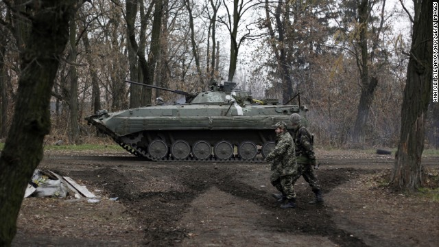Ukrainian servicemen walk past an armored personnel carrier in the village of Peski, Ukraine, on Wednesday, November 19. Fighting between Ukrainian troops and pro-Russian rebels in the country has left more than 4,000 people dead since mid-April, according to the United Nations.