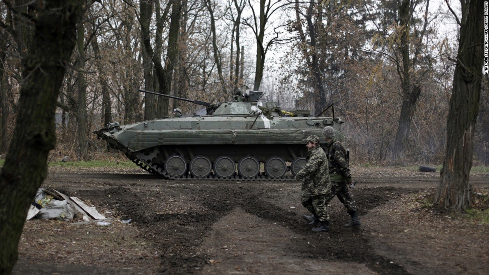 Ukrainian servicemen walk past an armored personnel carrier in the village of Peski, Ukraine, on Wednesday, November 19. Fighting between Ukrainian troops and pro-Russian rebels in the country has left more than 4,000 people dead since mid-April, <a href='http://www.ohchr.org/EN/NewsEvents/Pages/media.aspx?IsMediaPage=true' target='_blank'>according to the United Nations.</a>
