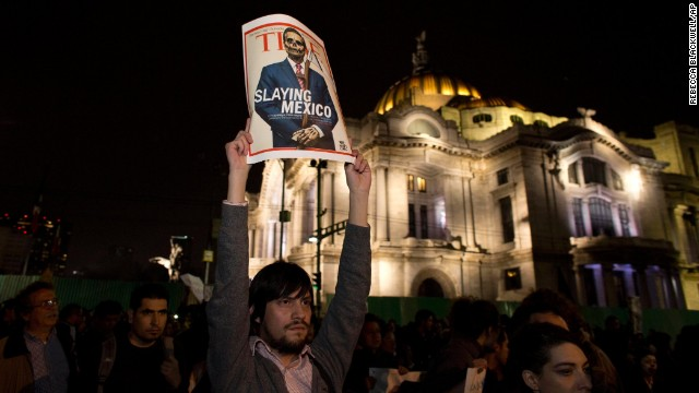 A protester holds up a poster parodying Mexico's President Enrique Peña Nieto during a rally in Mexico City on November 20.