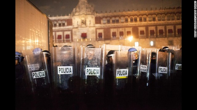 Police guard the National Palace in Mexico City as protesters and police clash.