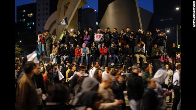 People on the base of a monument watch and cheer on marchers in Mexico City.