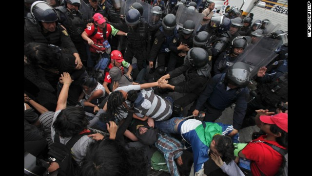 Riot police surround protesters who had thrown Molotov cocktails and destroyed vehicles in Mexico City.