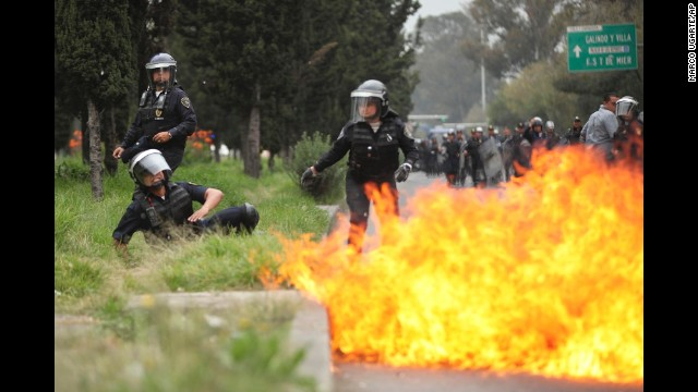 A police officer falls after a protester threw a Molotov cocktail.