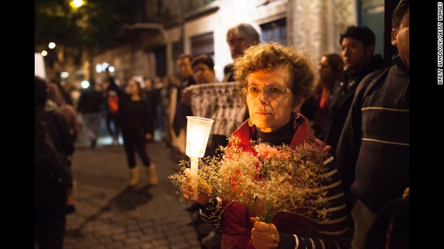 A woman holds flowers and a candle as marchers past during the November 20 demonstration.