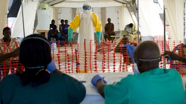 A health worker wearing a protective suit assists patients at an Ebola treatment center in Macenta, Guinea, on Friday, November 21.