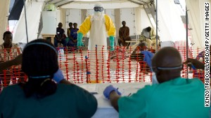 Caption:A health worker wearing a protective suit assists patients at the Ebola treatment centre run by French Red Cross in Macenta on November 21, 2014. The World Health Organisation said that 5,420 people have so far died of Ebola across eight countries, out of a total 15,145 cases of infection, since late December 2013. AFP PHOTO/KENZO TRIBOUILLARD (Photo credit should read KENZO TRIBOUILLARD/AFP/Getty Images)