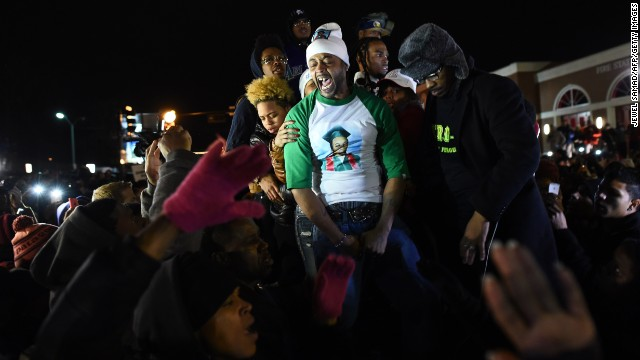 "Demonstrators gather outside the police station on November 24. The man in the green sleeves is Michael Brown's stepfather, Louis Head. In a video of the scene from the New York Times, Brown consoles a tearful McSpadden and then tells the crowd to ""burn this mother f---er down."""