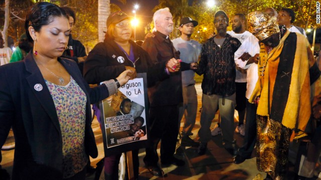 People hold hands in a prayer for peace at the Leimert Park area of Los Angeles.