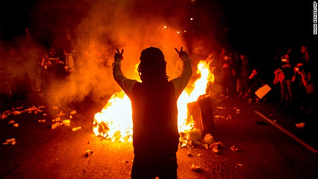 Demonstrators gather around a fire in the streets of Oakland on November 24.