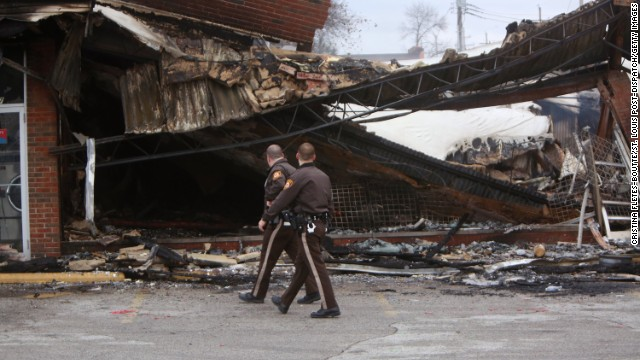Police officers walk past the smoldering remains of a beauty supply store on November 25.