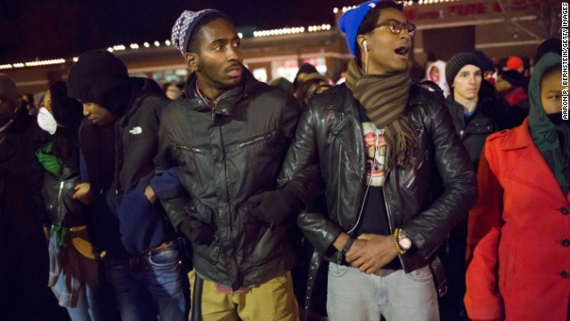 Protesters link arms in front of the Ferguson Police Department on November 25.