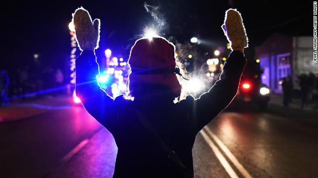 A protester holds her hands up in front of police on Tuesday, November 25.