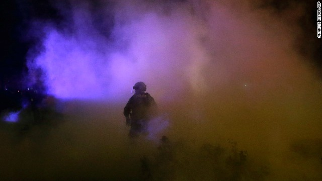Smoke engulfs a police officer on November 25.