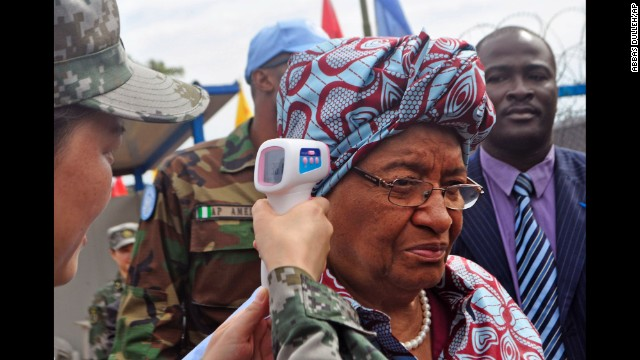 Liberian President Ellen Johnson Sirleaf has her temperature taken before the opening of a new Ebola clinic Tuesday, November 25, in Monrovia, Liberia.