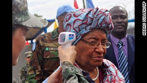 Liberian President Ellen Johnson Sirleaf has her temperature taken before the opening of a new Ebola virus clinic in Monrovia, Liberia, on Tuesday, November 25.