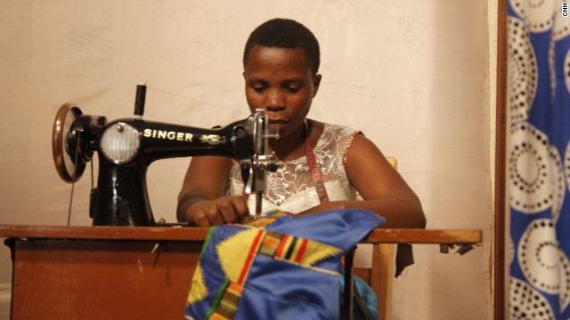 Mama Ngawerie helps Mbabazi tailor clothes to customers' exact needs in a private area of the shop.