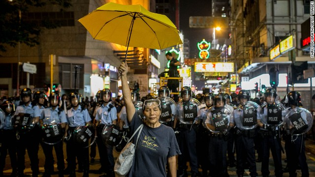 NOVEMBER 25 - HONG KONG: A pro-democracy activist holds a yellow umbrella in front of a police line on a street in Mong Kok district on November 25, 2014 in Hong Kong. Police and authorities have <a href='http://edition.cnn.com/2014/11/26/world/asia/hong-kong-protests-mong-kok/index.html'>started clearing barricades and tents</a> from the group's protest camp, almost <a href='http://www.cnn.com/2014/10/07/world/asia/hong-kong-protest-explainer/index.html'>two months after demonstrations began</a>.