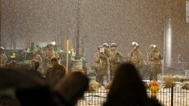 Snow falls as the Missouri National Guard watches protesters outside of the Ferguson Police Department on November 26.
