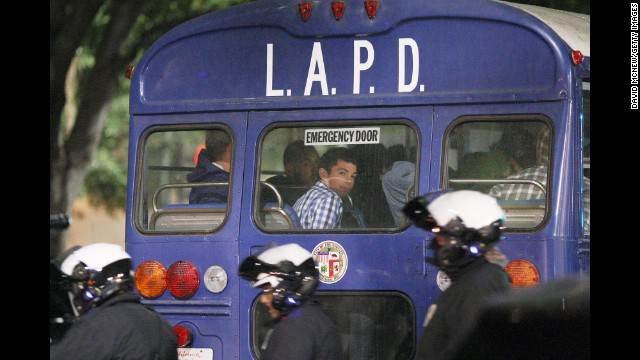 A protester sits in the back of a police bus after being arrested during a demonstration in Los Angeles on Wednesday, November 26.