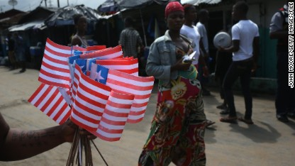 A woman sells Liberian flags on the street near an Ebola isolation ward on August 15, 2014 in Monrovia, Liberia. People suspected of contracting the Ebola virus are being brought by health workers to the center, a closed primary school originally built by USAID, while larger facililities are being constructed to house the surging number of patients. The Ebola epidemic has killed more than 1,000 people in four West African countries. (Photo by John Moore/Getty Images)