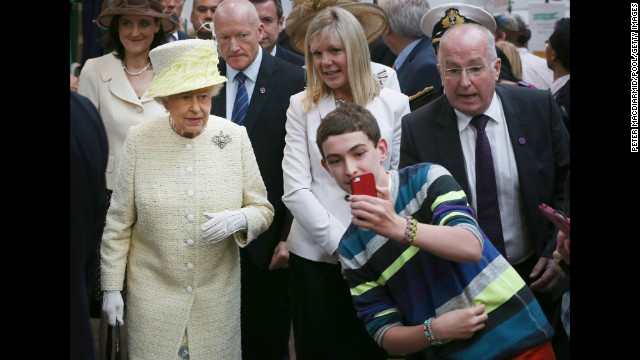 A boy in Belfast, Northern Ireland, takes a selfie in front of Britain's Queen Elizabeth II on Tuesday, June 24.
