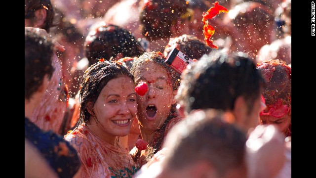 A tomato is about to hit two women as they take a selfie during a tomato fight in front of the Royal Palace in Amsterdam, Netherlands, on Sunday, September 14. The event was marketed as a protest of Russia's boycott of European produce.
