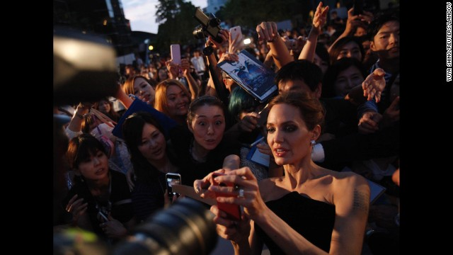"Actress Angelina Jolie tries to take pictures with fans as she attends the Tokyo premiere of her movie ""Maleficent"" on Monday, June 23. <a href='http://www.cnn.com/2013/05/14/showbiz/gallery/angelina-jolie/index.html' target='_blank'>See the life of Angelina Jolie</a>"