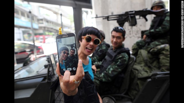 A woman takes a selfie in front of army soldiers standing guard in Bangkok, Thailand, on Tuesday, May 20. A couple of days later, Thailand's military declared it had taken control of the country in a coup.