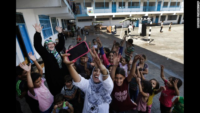 Volunteer Nisreen Shawa uses her phone to take a photo with displaced Palestinian children at a United Nations school in Gaza City on Thursday, August 7.