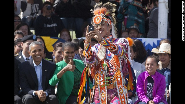 A Native American dancer takes a selfie Friday, June 13, in front of U.S. President Barack Obama, left, and first lady Michelle Obama at the Standing Rock Sioux Reservation in Cannon Ball, North Dakota.