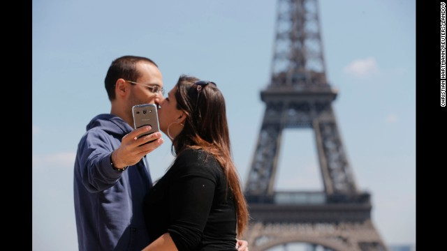 Tourists kiss in front of the Eiffel Tower in Paris on Friday, May 16.