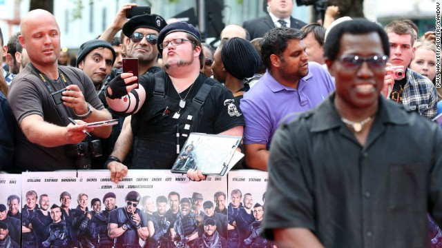 "Fans take selfies Monday, August 4, as actor Wesley Snipes, right, arrives for the world premiere of ""The Expendables 3"" in London."