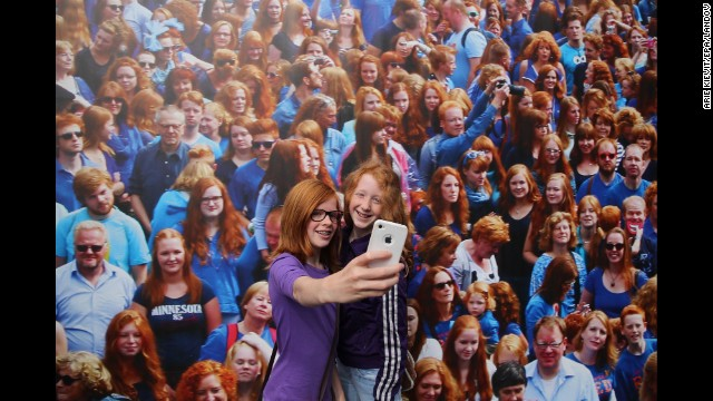"Two girls with red hair take a selfie in front of a picture while taking part in ""Redhead Days"" in Breda, Netherlands, on Sunday, September 7. <a href='http://www.redheaddays.nl/en/' target='_blank'>""Redhead Days""</a> is celebrated annually in the Dutch city, offering music, a fashion show, art exhibitions and other cultural events from and for the red-haired community."