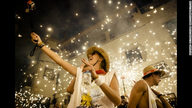 A girl takes a selfie in front of people setting off fireworks during a festival in Sitges, Spain, on Saturday, August 23.