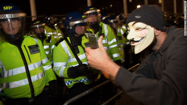 A protester snaps a selfie in front of police during the Million Mask March in London on Wednesday, November 5. The protest, organized by the activist group Anonymous, was said to be against austerity and the infringement of human rights.
