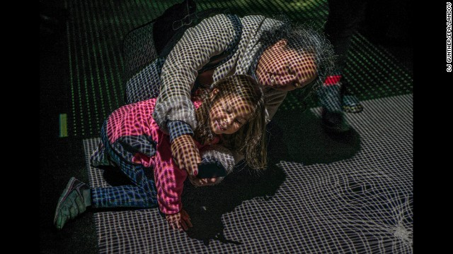 "A woman and child take a selfie while interacting with one of the light displays at the ""Illuminus"" art display in Boston on Saturday, October 25."