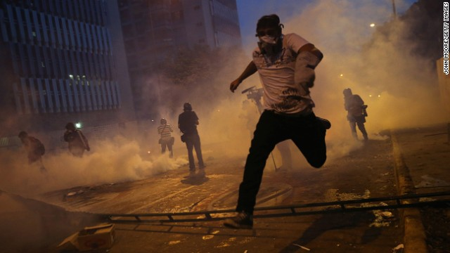 <strong>February 27:</strong> Protesters run from tear gas fired by the Venezuelan National Guard during an anti-government demonstration in Caracas, Venezuela. For months, protesters unhappy with Venezuela's economy and rising crime <a href='http://www.cnn.com/2014/02/18/world/gallery/venezuela-protests/index.html'>clashed with security forces.</a>