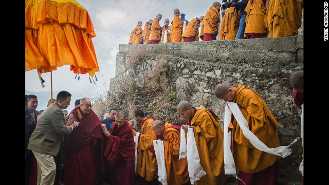 <strong>March 18:</strong> Tibetan Buddhist monks holding ceremonial scarfs stand in line to welcome the Dalai Lama as he arrives at a monastery in Shimla, India.