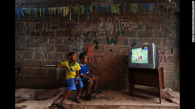<strong>June 17:</strong> Boys at a slum on the outskirts of Brasilia, Brazil, watch a World Cup soccer match between Brazil and Mexico. Brazil hosted this year's World Cup, although <a href='http://www.cnn.com/2014/06/12/world/gallery/world-cup-protests/index.html'>there were protests</a> over whether the money spent on the tournament would have been better used elsewhere.