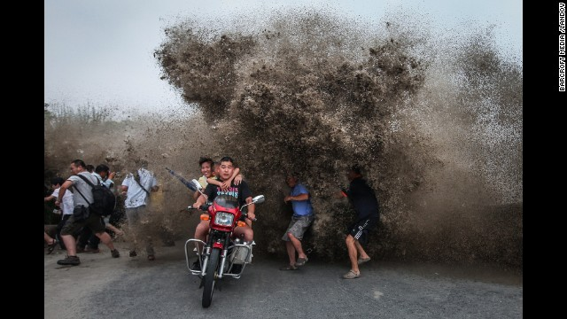 <strong>August 13:</strong> People run as a high wave hits the Qiantang River bank in Hangzhou, China.