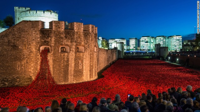 "<strong>November 7:</strong> Visitors view <a href='http://www.cnn.com/2014/08/04/europe/gallery/tower-of-london-art-installation/index.html'>the ceramic poppy installation</a> at the Tower of London. Thousands of ceramic poppies were installed in the dry moat surrounding the tower to mark the 100th anniversary of World War I. There were 888,246 poppies, one for each British military member that died during the war. The installation, called ""Blood Swept Lands and Seas of Red,"" was created by artist Paul Cummins."