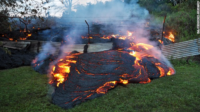 <strong>October 28:</strong> Lava from <a href='http://ift.tt/1DpTXpr'>the Kilauea volcano</a> pours past a boundary fence in Pahoa, Hawaii. The flow was picking up speed, prompting emergency officials to close part of the main road through town and tell residents to be prepared to evacuate.