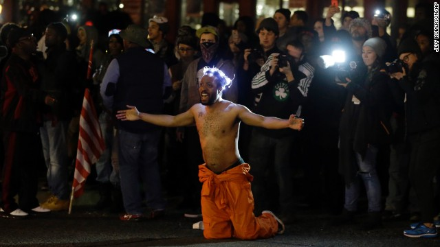 A man kneels in the middle of a street and yells at police before being arrested outside the police department in Ferguson, Missouri, on Saturday, November 29. Ferguson has struggled to return to normal since Michael Brown, an unarmed black teenager, was killed by Darren Wilson, a white police officer, on August 9. The grand jury's decision not to indict Wilson prompted new waves of protests in Ferguson and across the country.